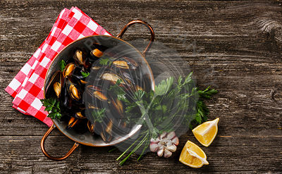 Mussels Clams in copper cooking dish pan on wooden background copy space