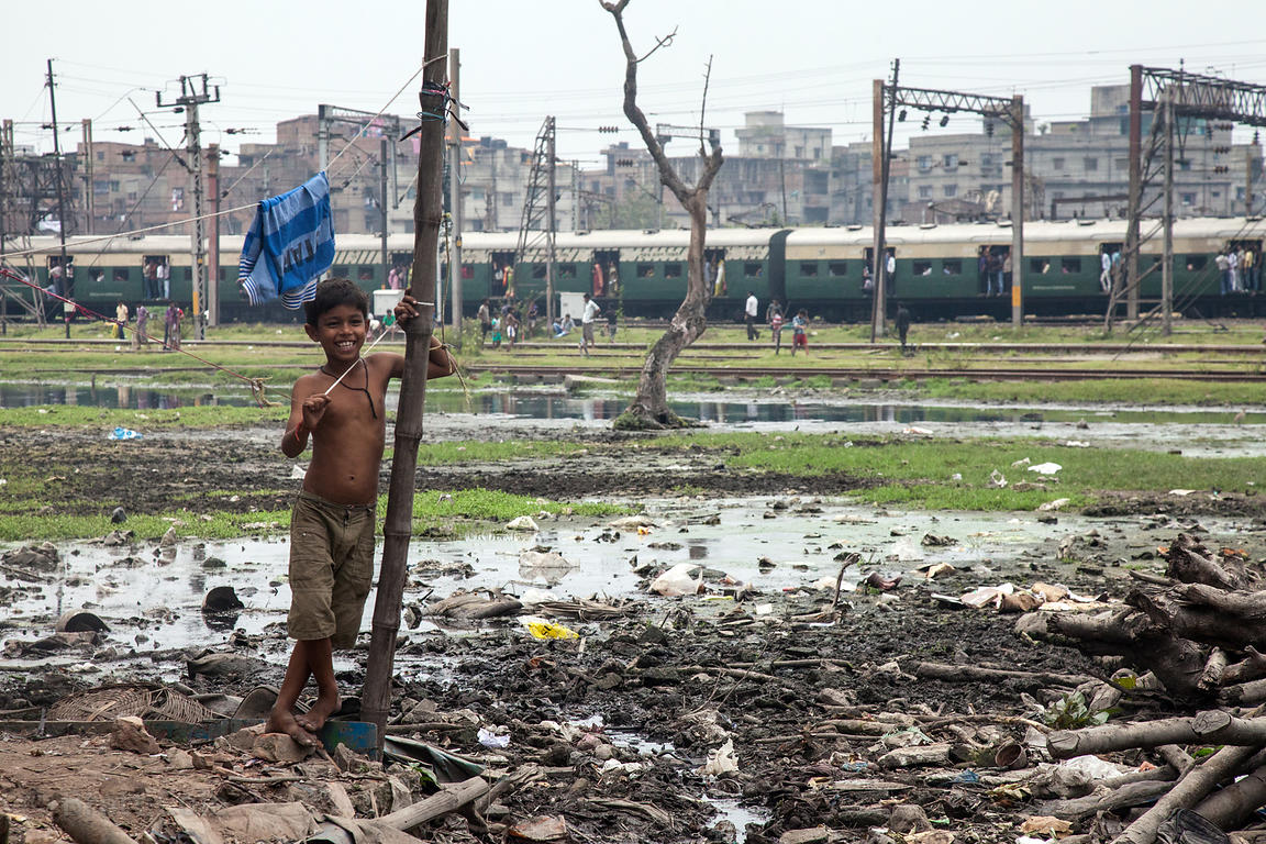 A boy stands in a bleak looking landscape in the Fakir Bagan slum area in Kolkata, India