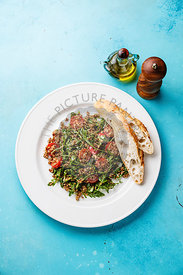 Salad with quinoa, tomato and arugula on white plate and bread on blue background