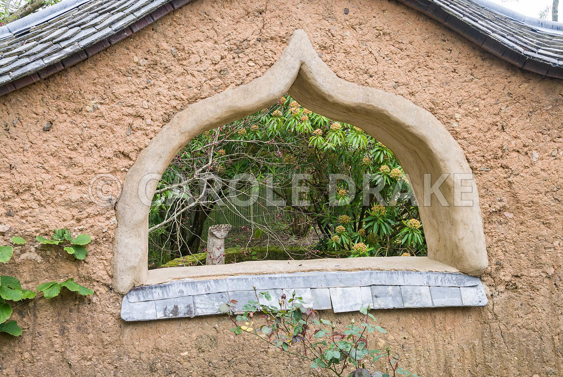 Ceramic figure by Carole Blackwel seen through 'window' in cob wall of the Pond Garden. Caervallack Farm, St Martin, Helston,...