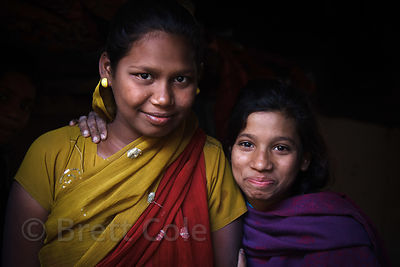 Two girls in a slum area in Ward 66, Muchipara, Kolkata, India. Many people in the community make sandals.