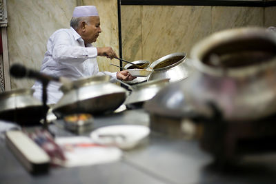 India - Delhi - Salahuddin, one of the directors at Karim's Restaurant serves food from pots