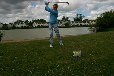 A resident at The Watermark, A Gated Community near Cirencester UK practices her swing in front of the village lake