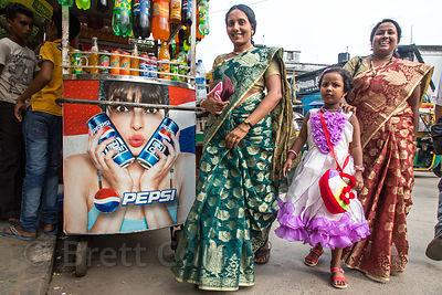 Family walks past a Pepsi ad in Gariahat, Kolkata, India. There is still a lot of resistance against sugary soft drinks in In...