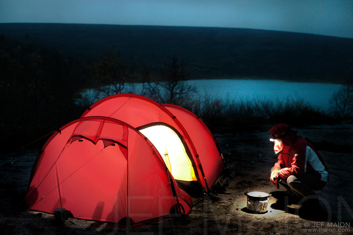 Backpacker cooking by tent by night