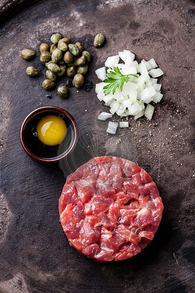 Beef tartar with capers and fresh onions on dark background