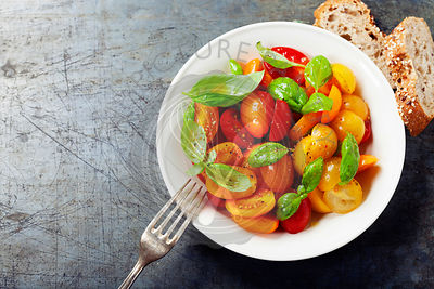 Fresh tomatoes with basil leaves in a bowl