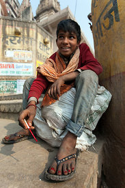A boy paints his toenails near Jain Ghat, Varanasi, India.