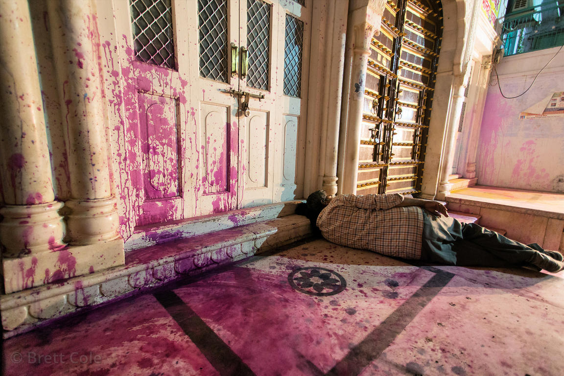 A man sleeps on the purple porch of a temple after the Holi Festival, Pushkar, Rajasthan, India