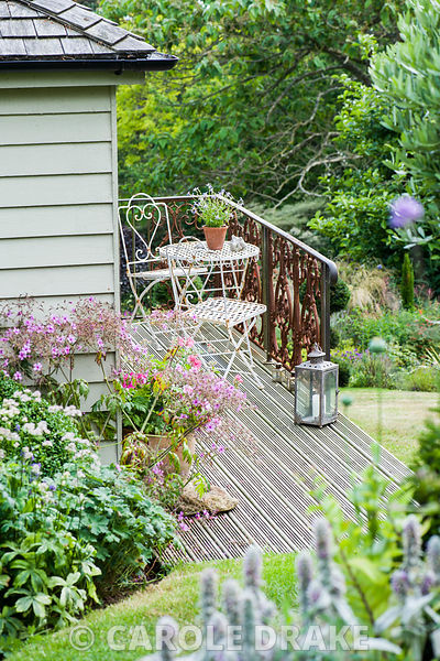 Small decked seating area outside Debbie's home studio, a third of a way down the sloping garden.