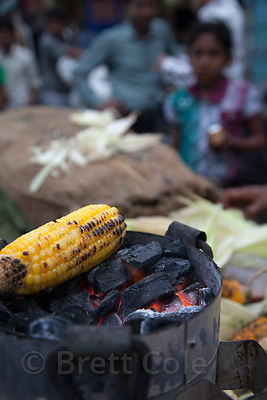 Corn is roasted on coals at a market in the Dharavi slum, Mumbai, India.