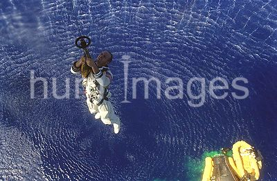 (29 Aug. 1965) --- Astronaut Charles Conrad Jr. is hoisted up to a Navy helicopter while astronaut L. Gordon Cooper Jr. waits...