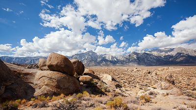 Medium Shot: Blue Skies, Fluffy White Clouds, & the Wind Swept Sandstone of the Alabama Hills Along the Majestic Sierras