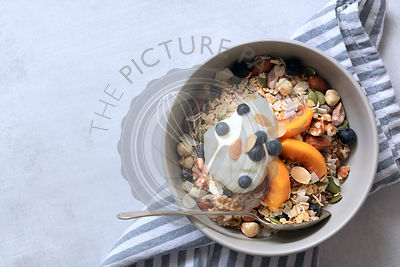 Breakfast bowl of wholegrain cereal, yogurt, fresh fruit and nuts on a pale blue textured background with copyspace.