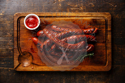 Grilled roasted sausages and ketchup sauce on cutting board on wooden background