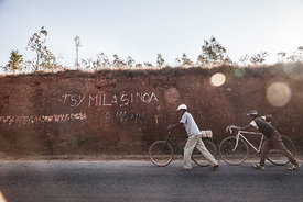 "Men walk past graffiti reading ""We don't need Chinese"" in Soamahamanina (70 kilometer from Antananarivo) on September 29, 201..."