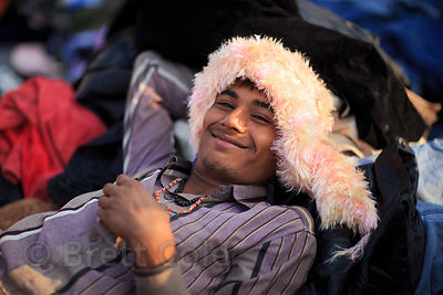 Happy salesperson at a used clothing market, Pushkar, Rajasthan, India