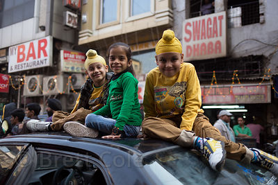Children sit atop a car during a Sikh festival in Delhi, India