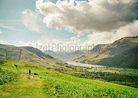A hiker walking over Rannerdale Knotts on a sunny day in the English Lake District, UK.