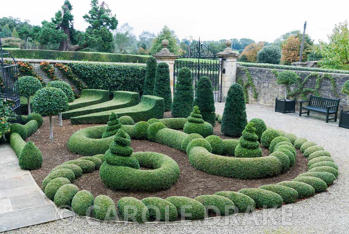 Clipped box and yew in the Parterre Garden punctuated by standard laurels with wall trained pyracantha behind. Gazebo and gat...