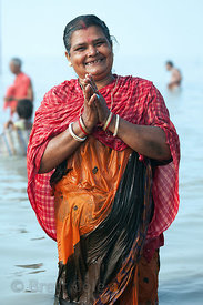A woman prays in the Bay of Bengal at the Gangasagar Mela (festival), a pilgrimage to Sagar Island in India, where the Ganges...