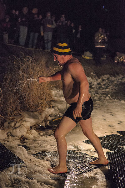 Nick Bedell leaves the frigid water during the Hawkeye Wrestling Club's Polar Plunge at the Brown Deer Country Club in Coralv...
