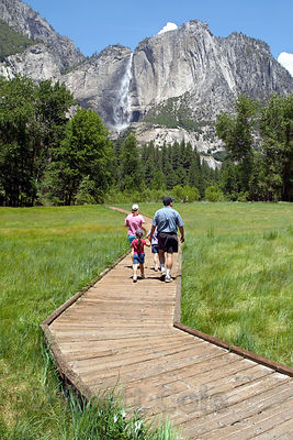 A family walks along a boardwalk to view Yosemite Falls, the tallest waterfall in the US. Yosemite National Park, California.