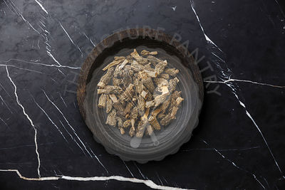 Dried morel mushroom on wooden plate on dark marble background
