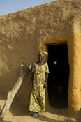 woman standing at the entrance of a typical mud house, île à Morphil, Senegal