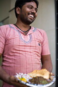 India - Delhi - A man holds a plate of chole bhature at Sitaram chole bhature wala