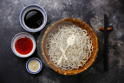 Raw Udon noodles in bamboo basket with sauces and sesame on dark background copy space
