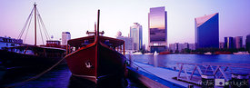Panoramic evening shot of traditional abra's against Dubai's skyline.