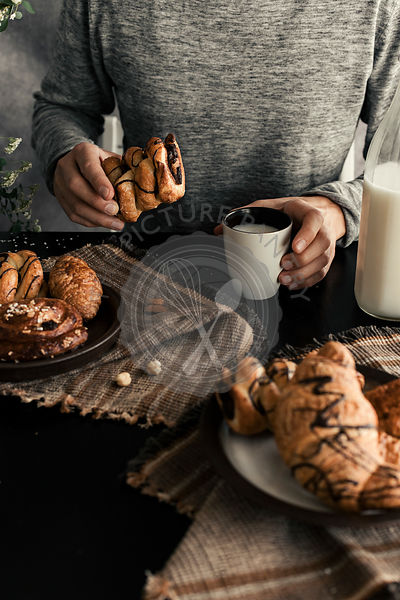 MAN HOLDING FRESH BAKED CROISSANT WITH CHOCOLATE