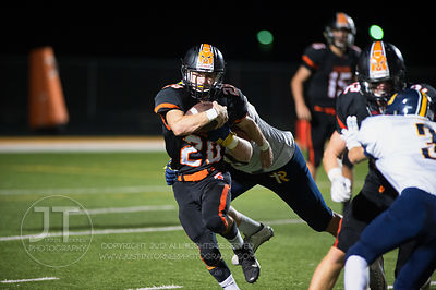Solon's Hunter Kula (28) slips a tackle by Iowa City Regina during a long run during the first half of play in Solon on Frida...