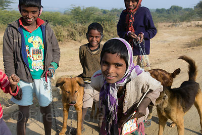 Children walk dogs in the desert in remote Kawalai village, Rajasthan, India