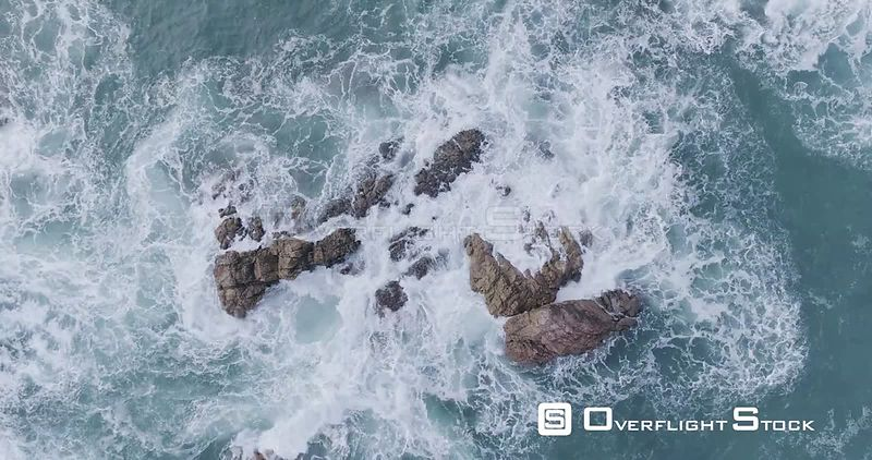 Aerial drone looking down at rocks jetting out of the ocean waves off the coast of Portugal