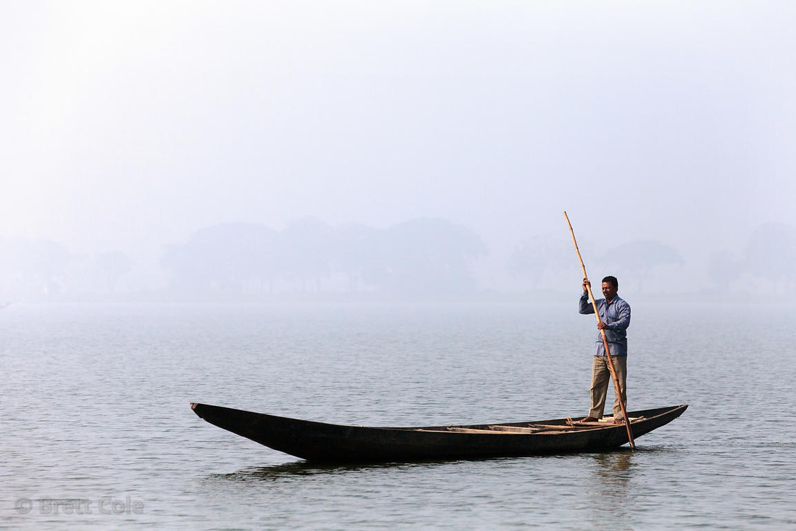 A fisherman in the East Kolkata Wetlands, Kolkata, India. They use the poles for propulsion and to scare up fish by beating t...