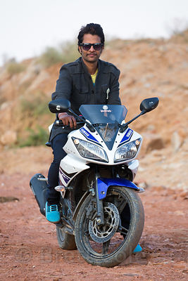 A man poses proudly on his motorcycle in the Thar Desert, near Kharekhari village, Rajasthan, India