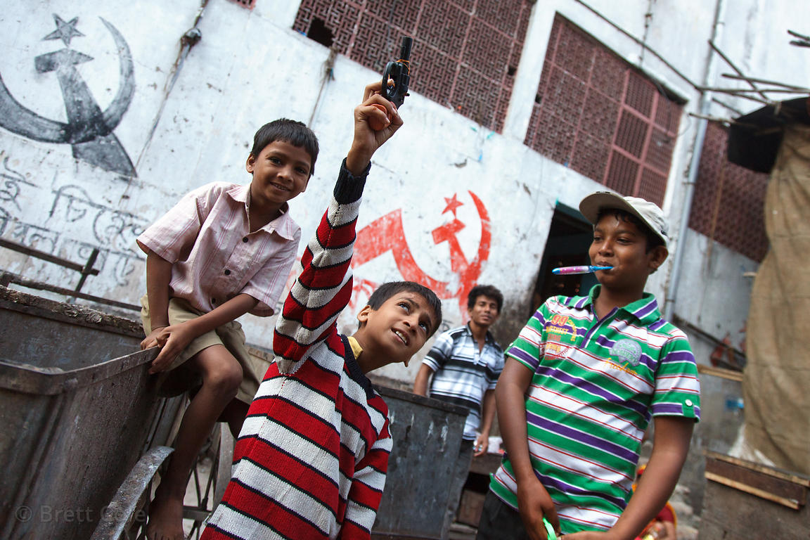 Boys joke around as one of them gestures with a toy gun, in front of a wall with Communist party political logos, Newmarket, ...