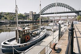NEWCASTLE UPON TYNE, ENGLAND, UK - MAY 08, 2018: Fishing traweler moored on Newcastle Quayside with the Tyne Bridge in the ba...