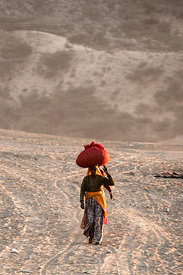 A woman carries a bumdle on her head down a sandy trail in the desert, Pushkar, Rajasthan, India