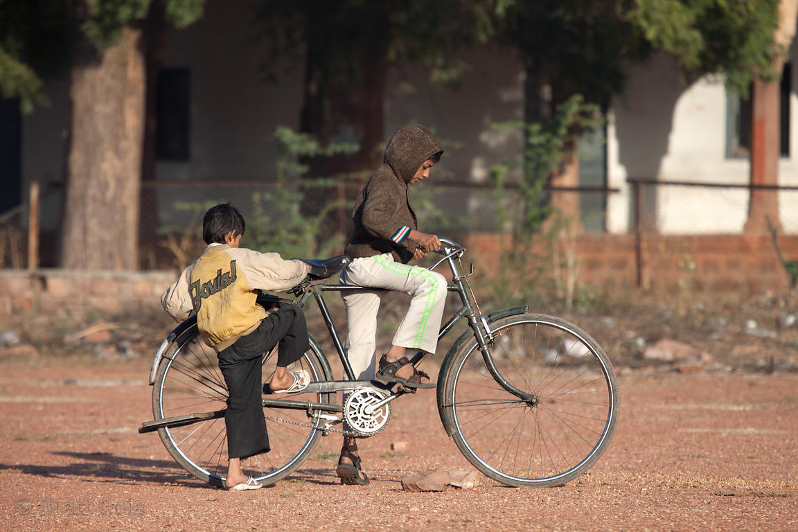 Two boys ride an oversize bike in a cricket field, Jodhpur, Rajasthan, India
