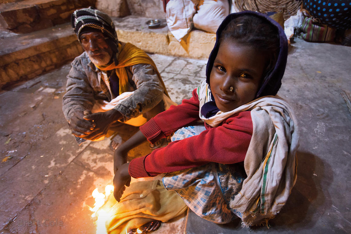 A father and daughter stay warm by a fire at Dashashwamedh Ghat, Varanasi, India.