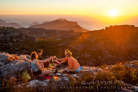 Four ladies having a picnic on a mountain summit at sunrise, cheering with glasses of wine