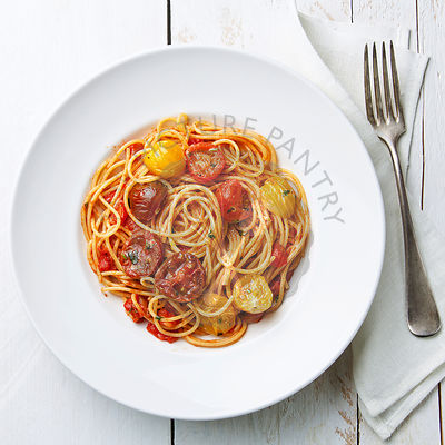 Spaghetti with tomato sauce on white wooden background