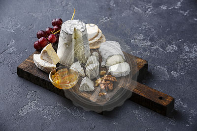 Goat Cheese board Snack assortment with confiture and grape on cutting board on black background