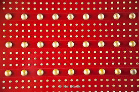 A graphic pattern of gold dots on a red door found in the city of Xi'an in China.