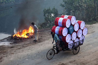 A man drives barrels past a fire in Dhapa, Kolkata, India. Dhapa is the site of Kolkata's largest landfill, and numerous recy...