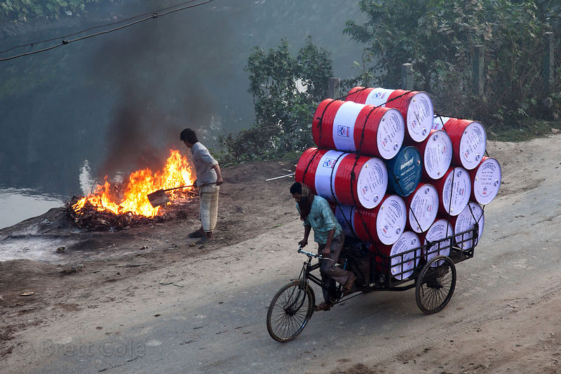 A man drives barrels past a fire in Dhapa, Kolkata, India. Dhapa is the site of Kolkata's largest landfill, and numerous recycling and incineration operations.