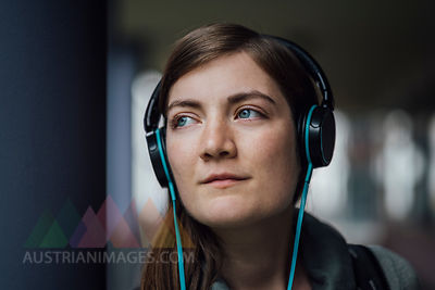 Portrait of daydreaming young woman listening music with headphones